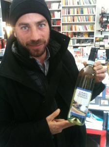 Pietro mostra con orgoglio la bottiglia personalizzata dai librai di Therese-Profumi per la mente di Torino.